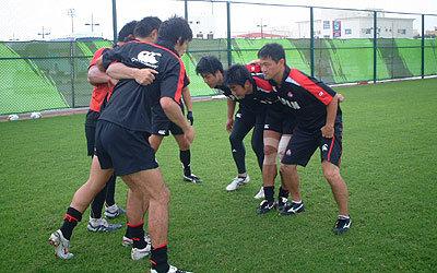 スクラム練習で自ら身体を張って指導する佐野監督(右)