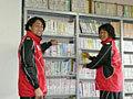 小学校の控室の本棚をのぞく大野選手と菊谷選手